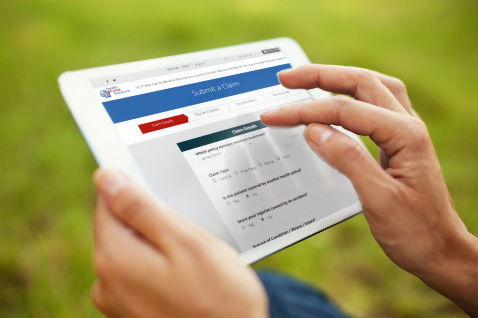 close up of hands touching an ipad to submit a claim while person is outside on the grass