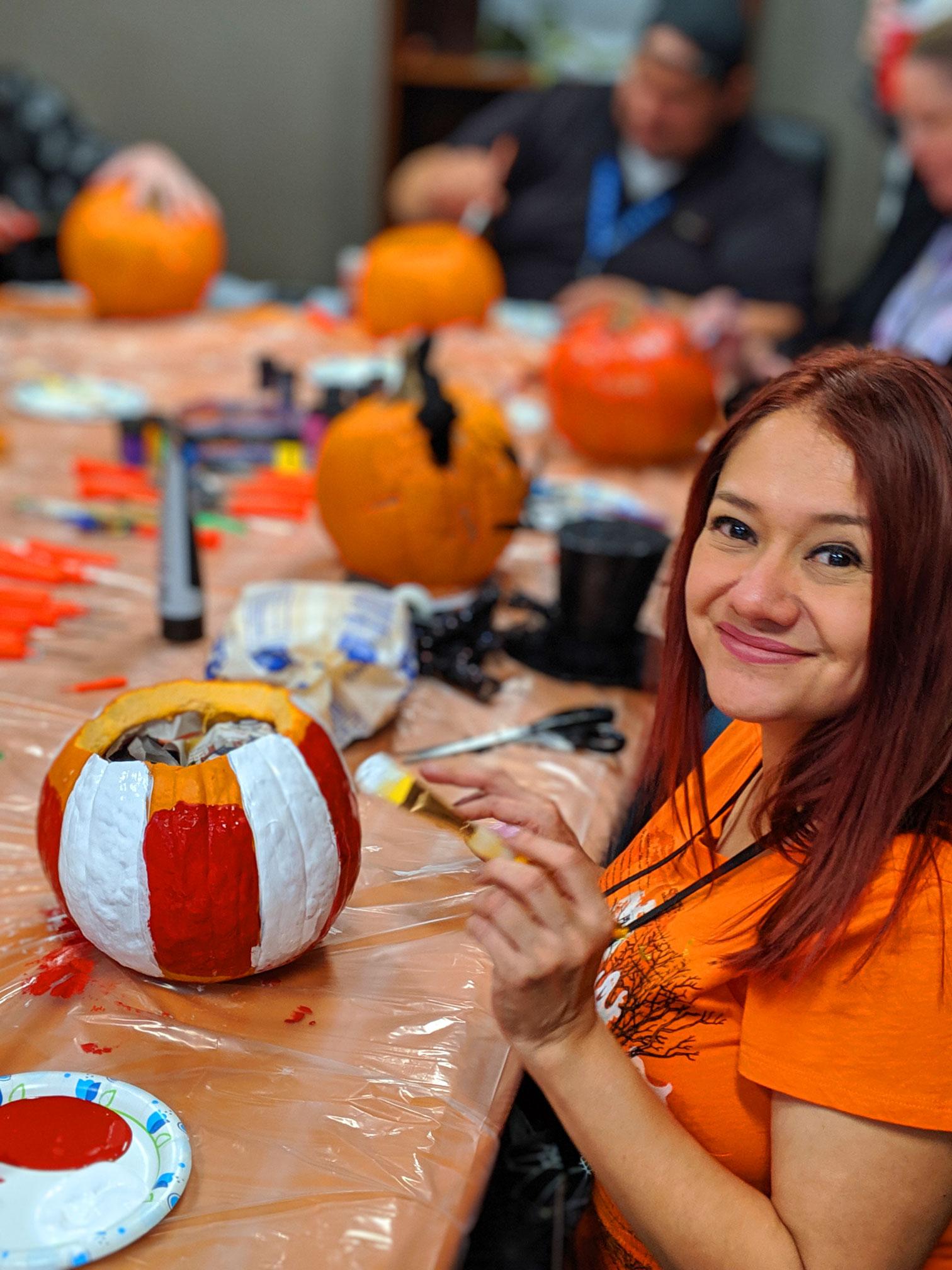 happy employee painting a pumpkin