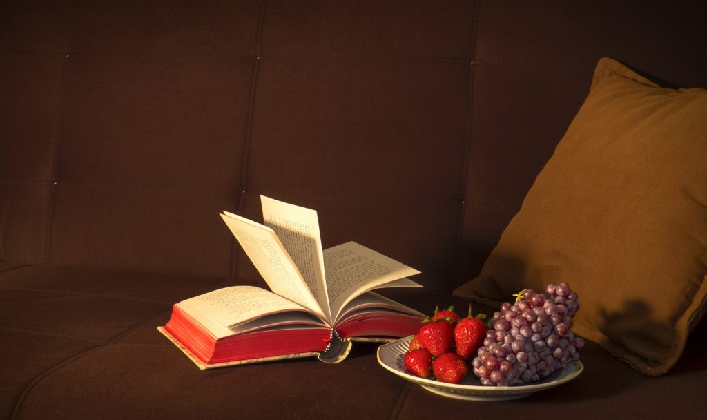 open book on a sofa next to a bowl of fruit