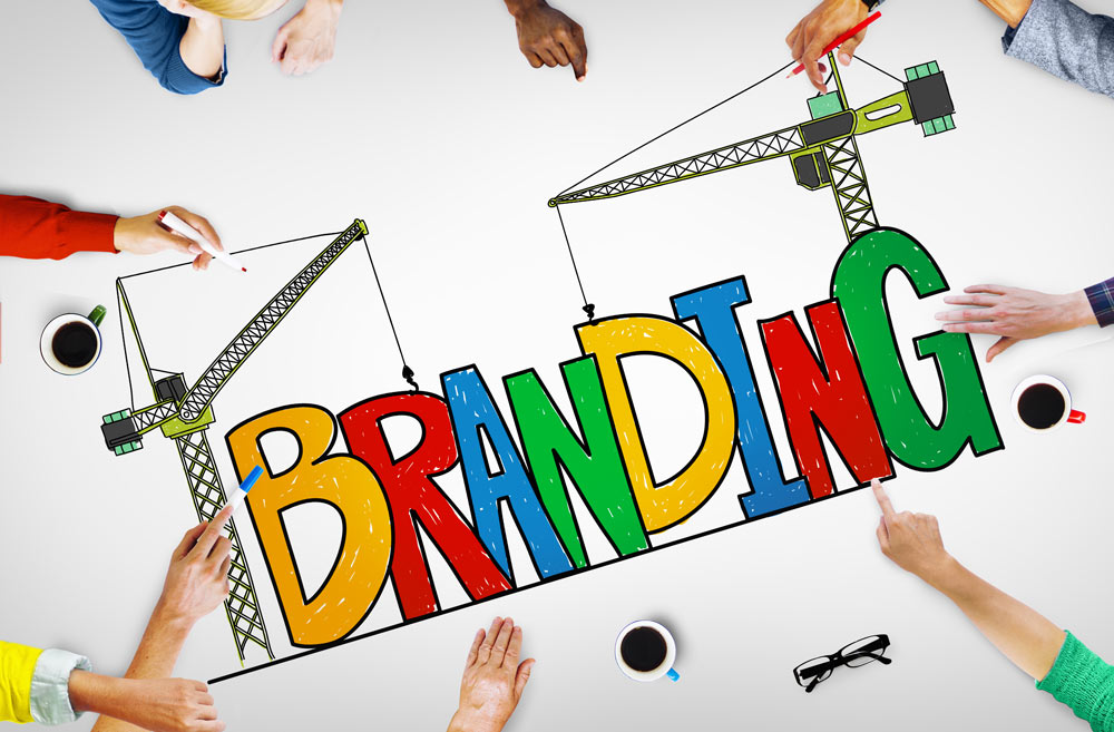 various hands around a drawing board, spelling out the word -branding-