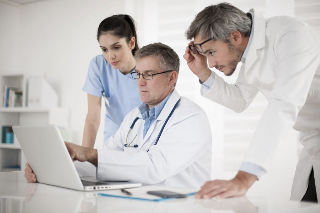 Medical practioners surrounding a laptop