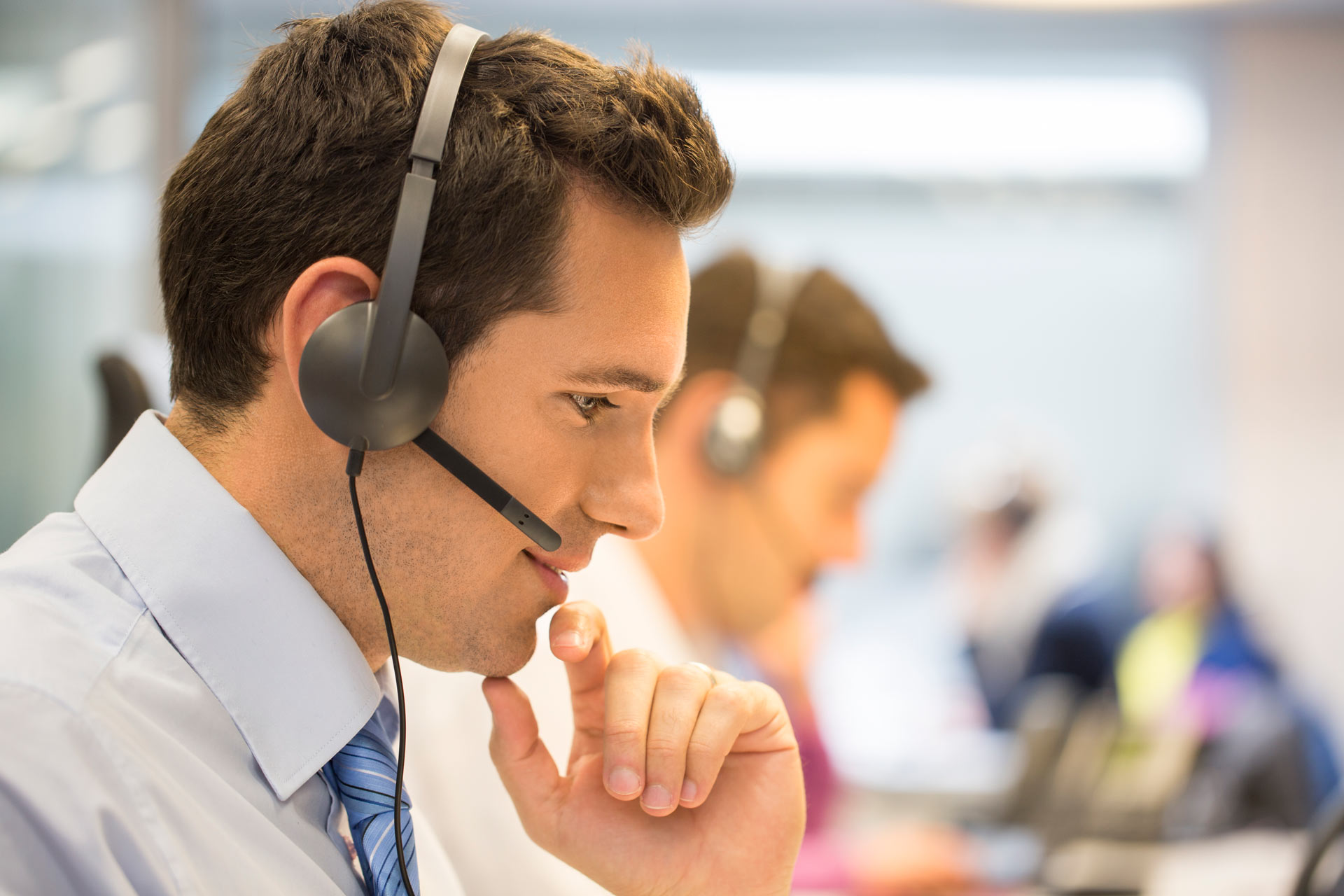 businessman with a phone headset on, sitting in an open floor plan office