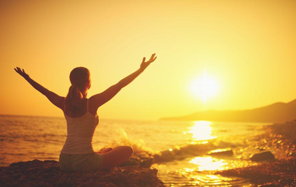 yoga at sunset on the beach. woman doing yoga, performing asanas and enjoying life on the sea