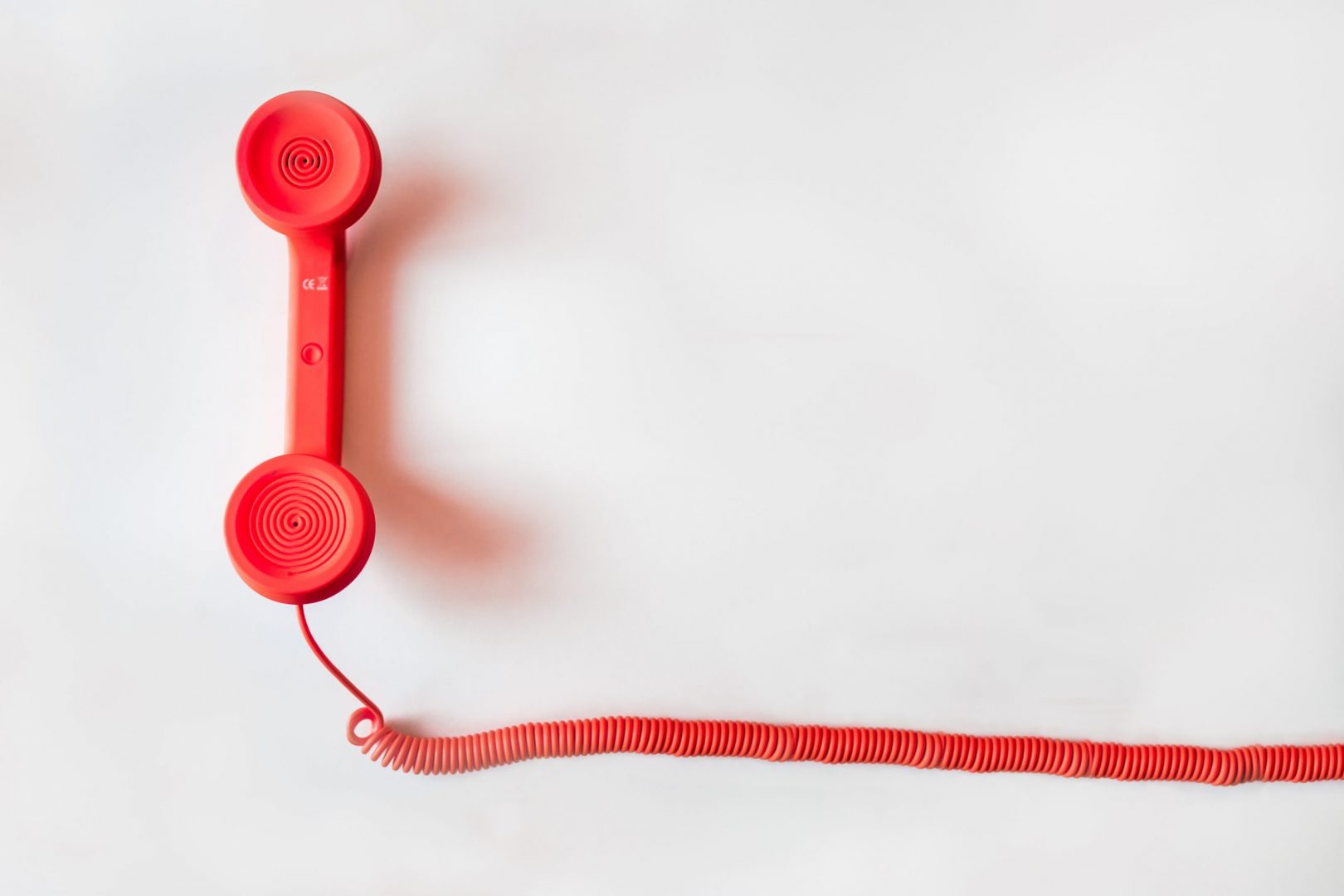 red corded phone with cord trailing off the camera screen