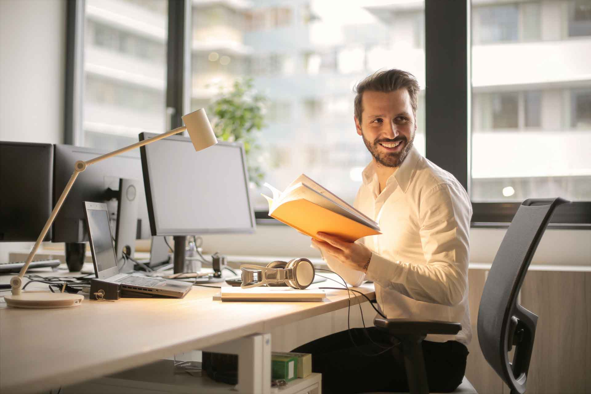 Smiling man sitting at computer desk while reading a book