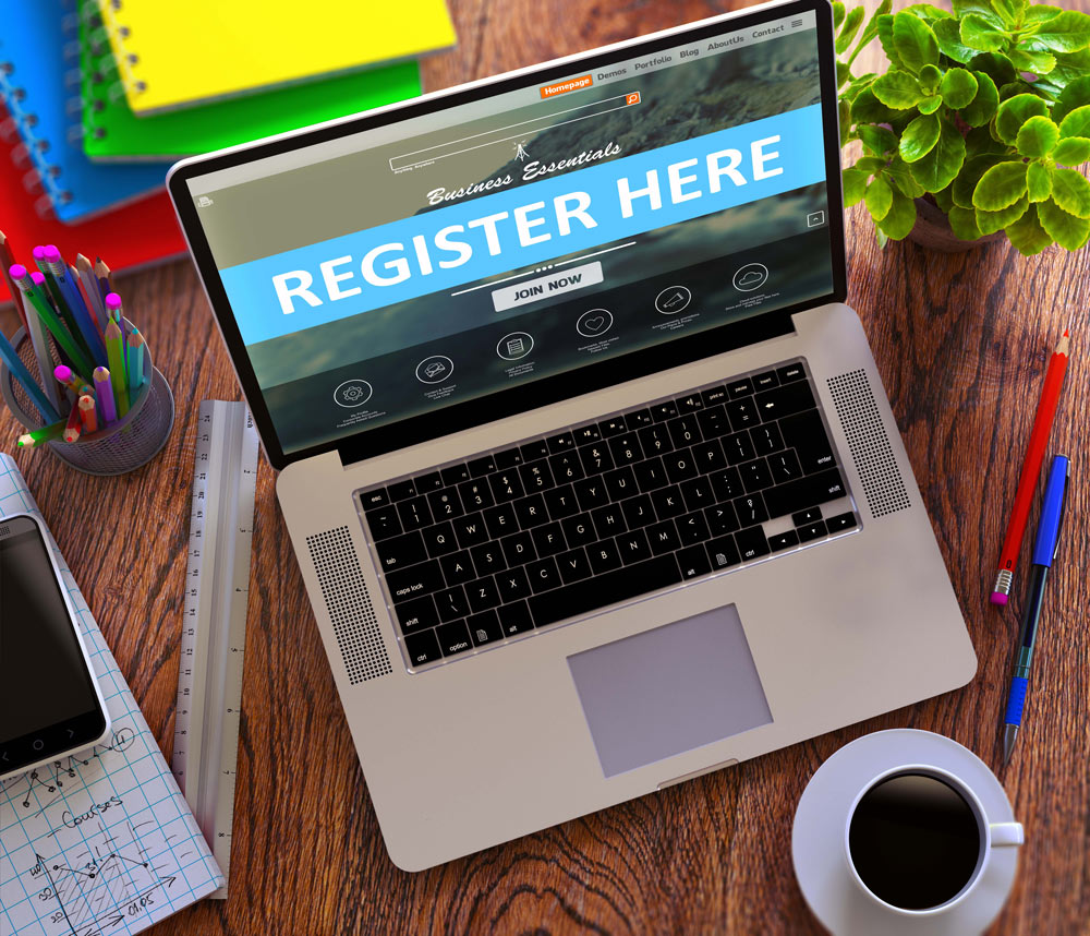 laptop with -register here- text on the screen