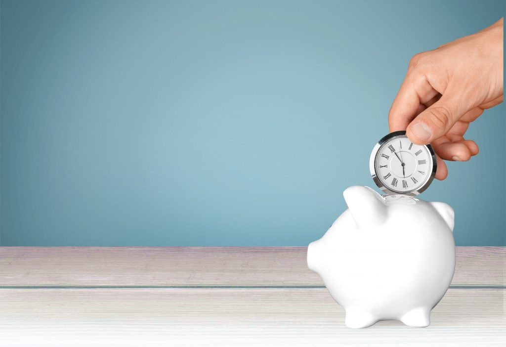 hand inserting a small clock into a piggy bank